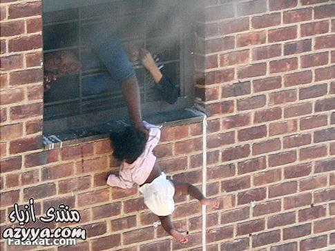 أم تدلي طفلتها خارج الشقة التي تحترق حتى لاتختنق إنها
